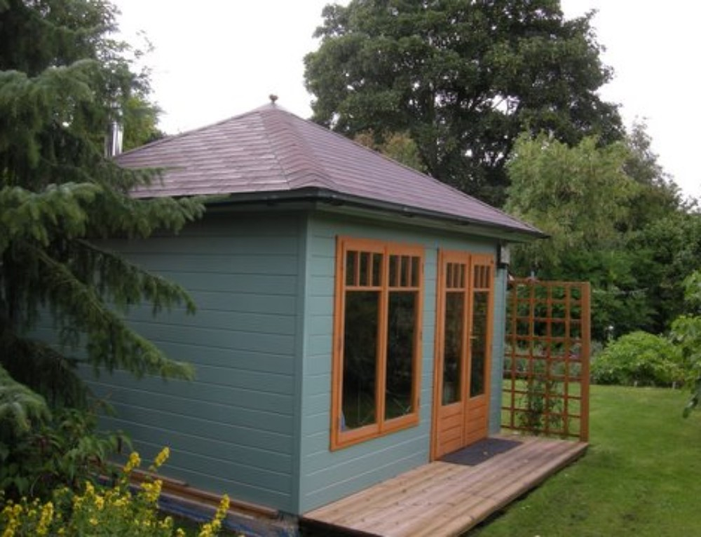 A cosy garden office with a wood burning stove