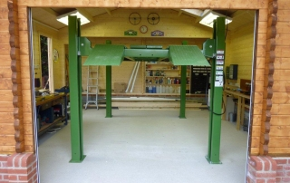 Classic log cabin garage with car lift