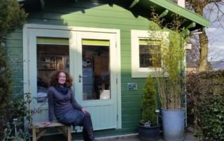 Lucy outside print studio log cabin