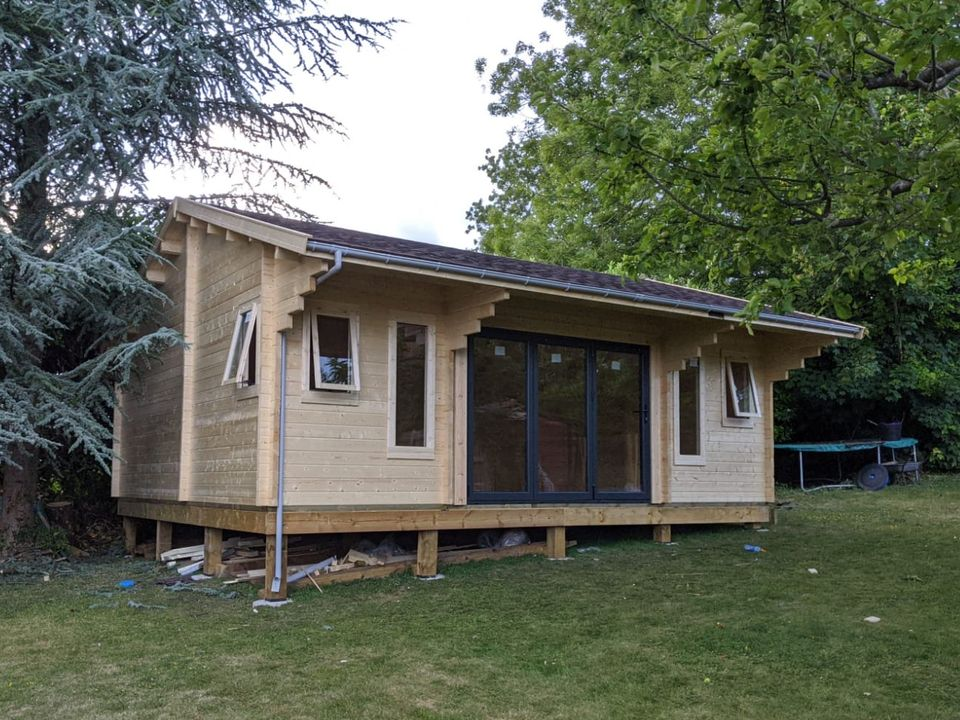 Grey gutters on a Classic log cabin with eaves canopy